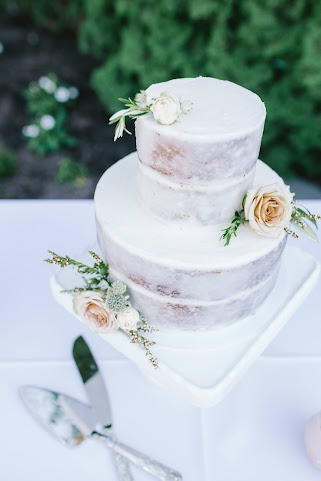 classic nearly naked cake with lush white and beige blooms for a white garden wedding in Utah