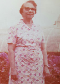 Grainy photo of Nicole's maternal grandmother outside in a housecoat