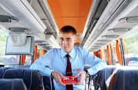 Elinde bir yolcu biletiyle otobüs içinde gülümseyen bir muavin