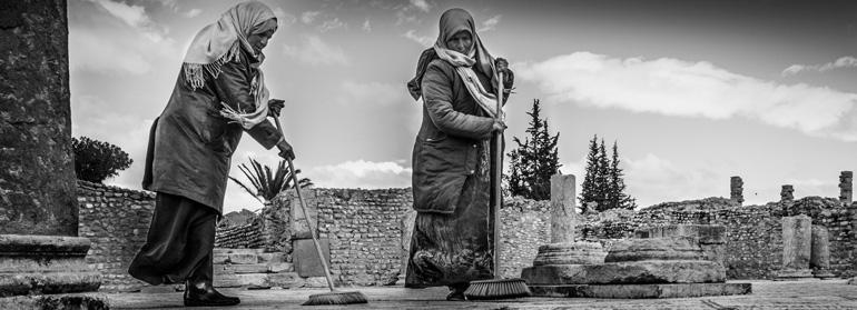 Photo panoramique de femmes balayant les vestiges archéologiques de Sbeïtla en Tunisie