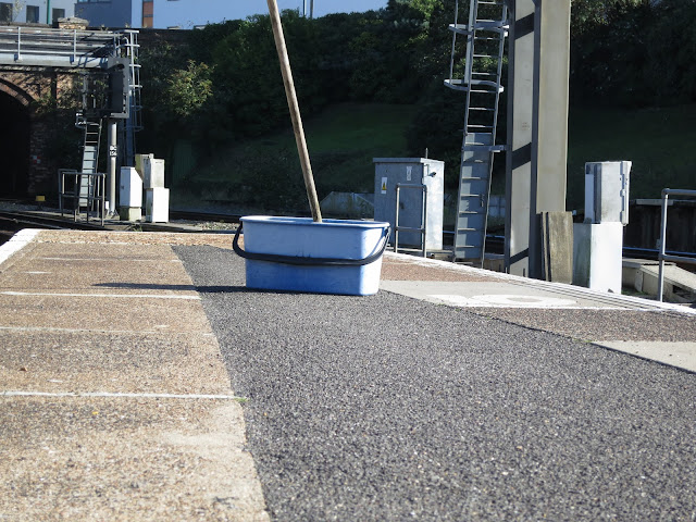 Blue Bucket with mop at far end of station platform with gantry and tunnel.