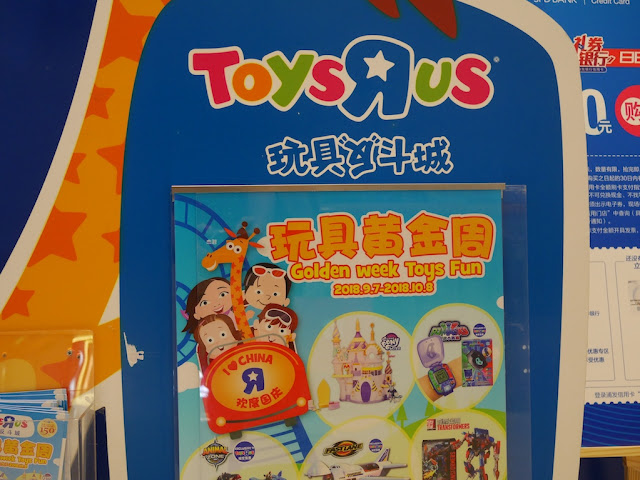 "Portion of Toys ""R"" Us ""Golden week Toys Fun"" sign with ""I ♥ China"" rollercoaster"