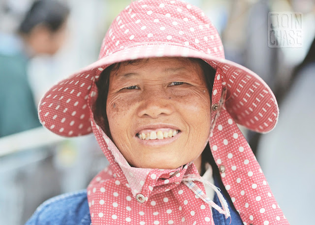 A Thai woman with a wide grin by the area where Thailand, Laos, and Myanmar meet.