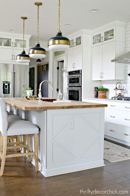 Gray island white cabinets brass accents