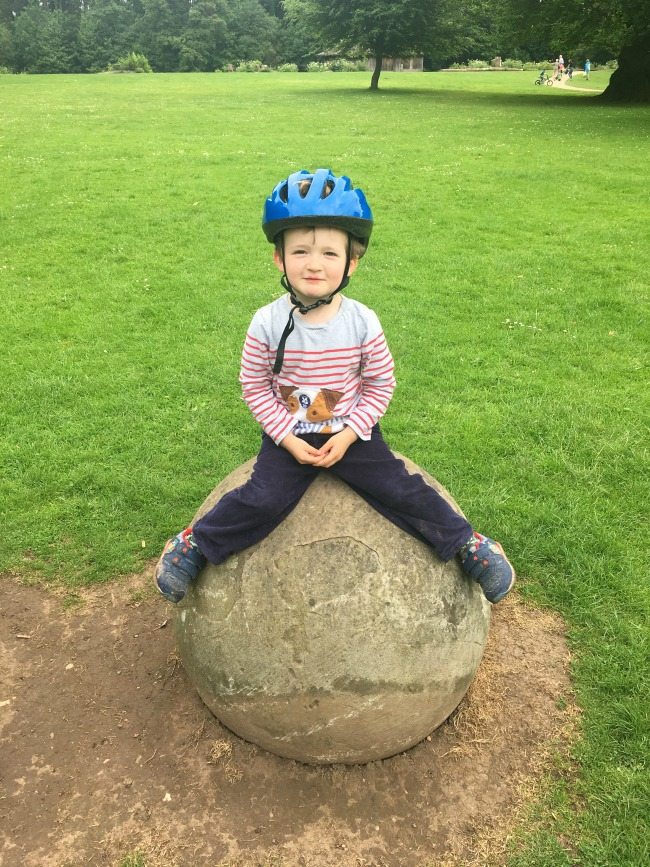 toddler-sat-on-stone-ball-at-Tredegar-park