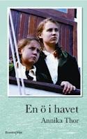 Omslag till En ö i havet. Två flickor med flätor och matchande kläder står på en båt och tittar in mot land.