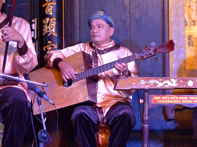 Musician playing traditional instrument during performance in Hoi An