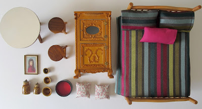 Selection of modern pink, red and wooden dolls' house miniatures arranged on a desktop.