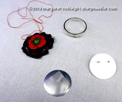 Embroidered remembrance poppy along with the parts of the pin setting. Poppy is ready to be mounted in pin setting.