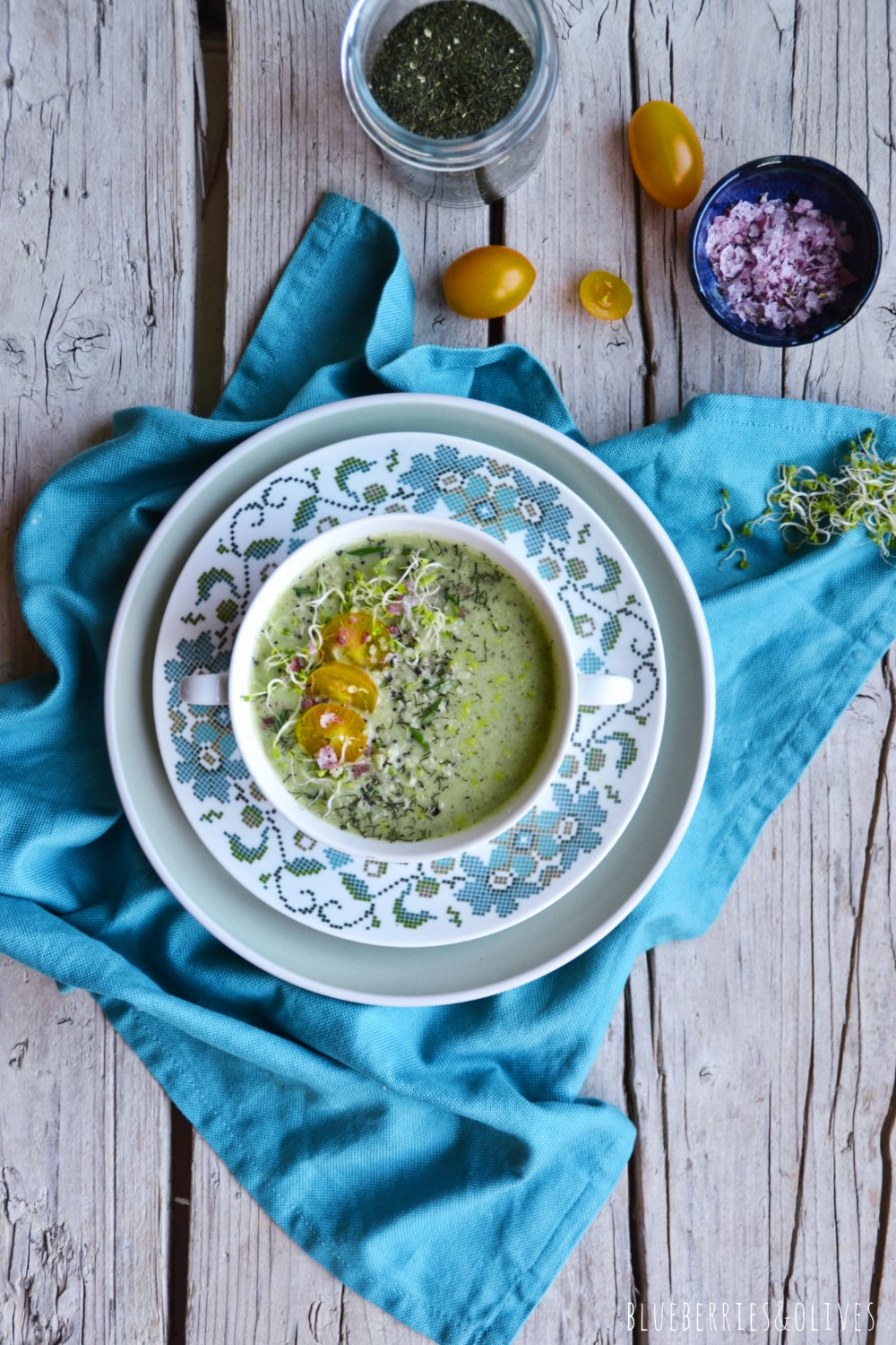 flat lay cold raw soup in vintage colorful porcelain bowl, blue tablecloth, yellow tomatoes
