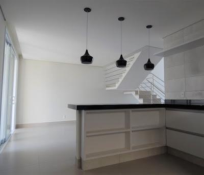 A sala de jantar, vista pela cozinha, fica entre a varanda e a sala de estar, sendo separada desta pela escada de perfil aparente.