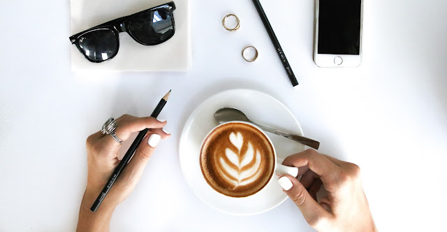 woman writing and drinking coffee