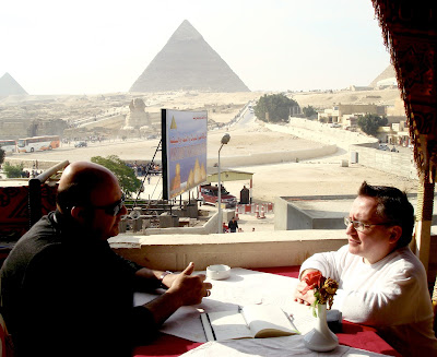 Simon sits opposite an Egyptian man in a coffee shop with the pyramids in the background.