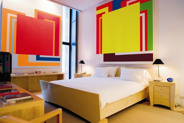 Photo of one of the bedrooms with wooden bed and large colorful photos on the walls