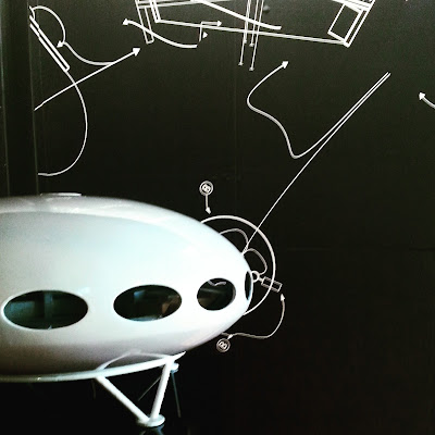 Model of a Futuro House in front of a wall of sketches of its design.