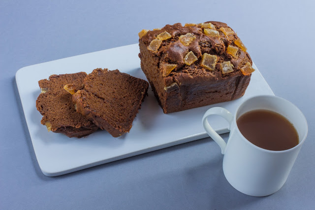 A ginger cake loaf partially sliced and a cup of tea
