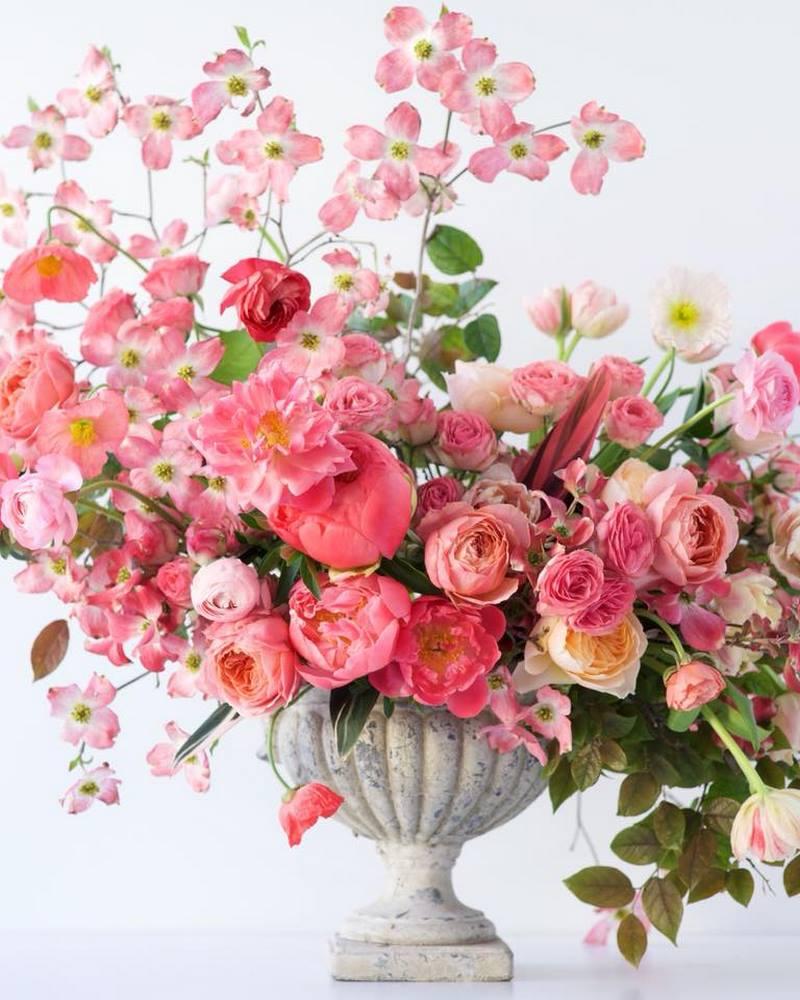 jarrón de piedra y flores de color rosa