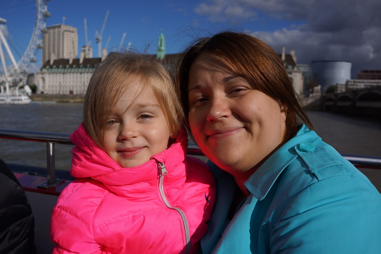 mum and daughter wearing colourful jackets in front of london eye