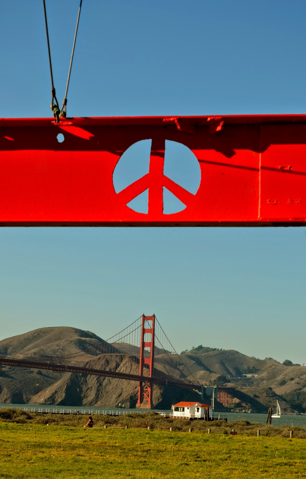 A peace sign in a Mark di Suvero sculpture at Chrissy Field with the Golden Gate Bridge in the background