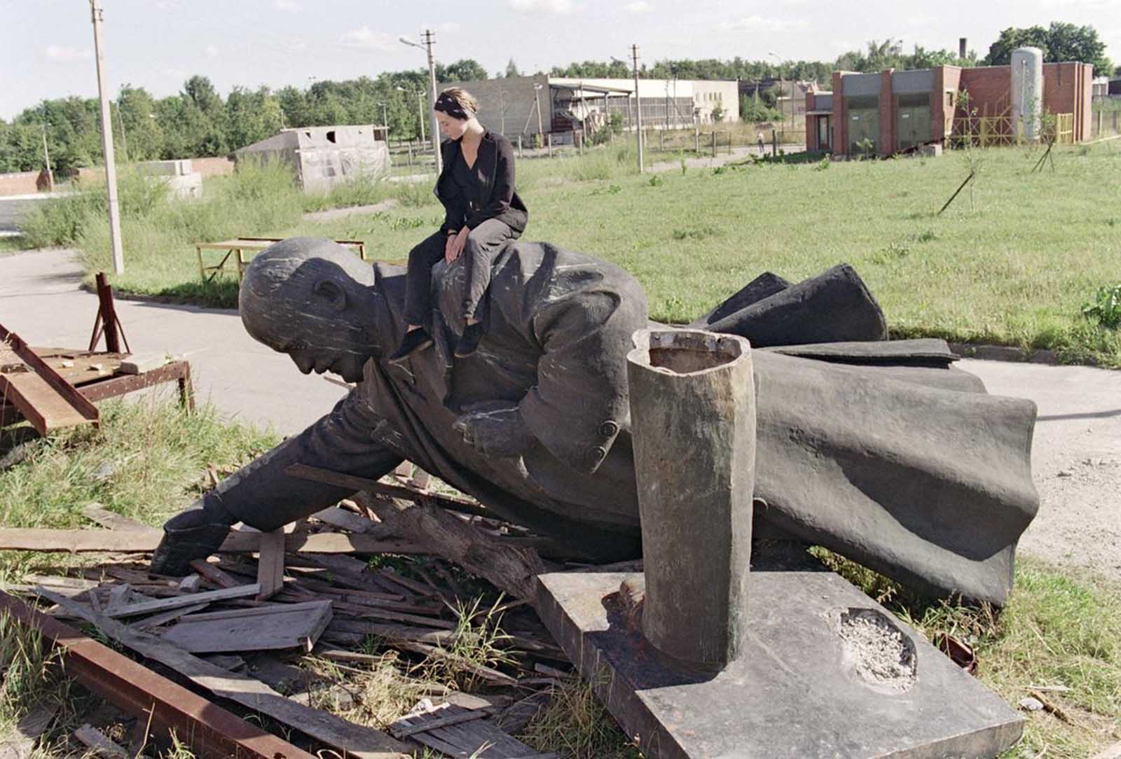 A young Lithuanian girl sits on the toppled statue of Russian Bolshevik revolutionary leader Vladimir Lenin in Vilnius after the monument was removed from the center of the Lithuanian capital, on September 1, 1991.
