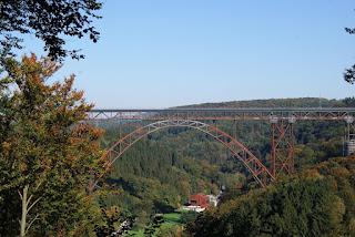 Eine große Stahlbrücke spannt sich über das Tal der Wupper. Darunter befindet sich eine Freizeitgaststätte