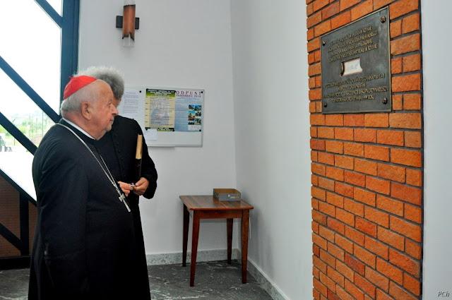Kardynał Dziwisz ogląda pamiątkową tablicę umieszczoną na ceglanej ścianie