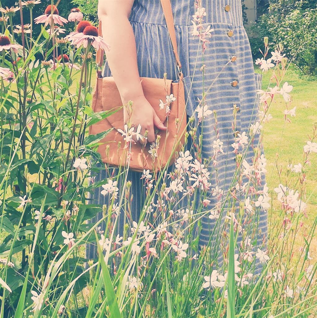 Sukienka w paski i torebka z washpapy w letnim ogrodzie. Nowoczesność i klasyka