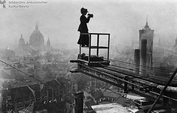 Photograph of woman with camera standing on high-rise construction beam, Berlin, 1910