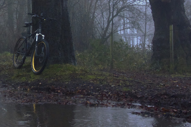 cycling in the rain by a puddle