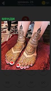 У девушки на ногах сделано менди, красивые узоры покрывают половину ног