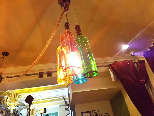 Close up of some lights in The Trading House Glasgow. The light shades are made out of glass bottles.