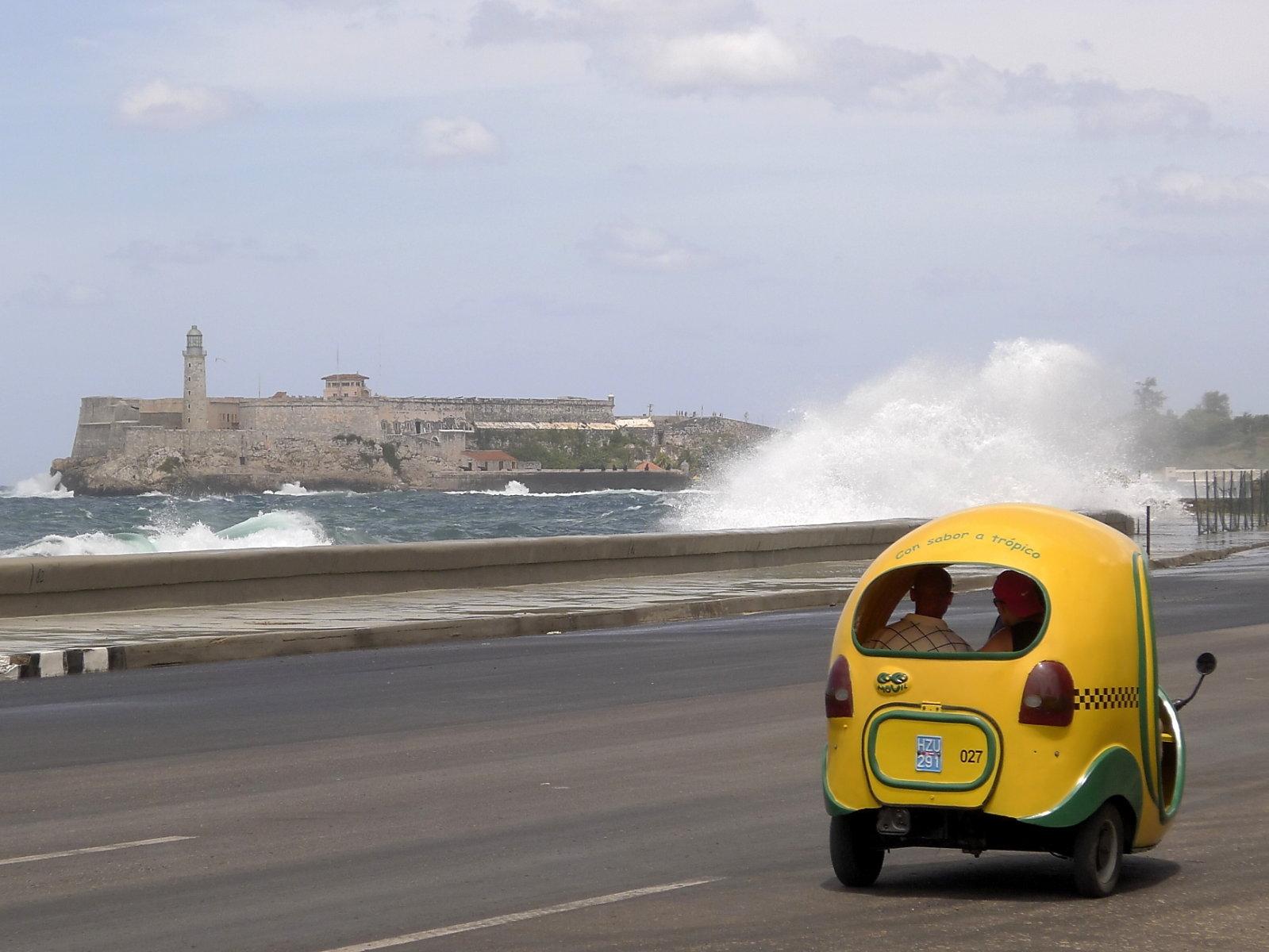 Gischt spritzt über den Malecón, vorbeifahrendes Cocotaxi