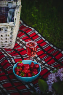 Red, white, and blue blanket, white basket, juicy red strawberries in a blue bowl
