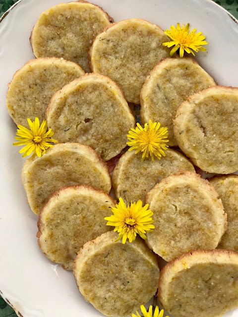 Finished cookies on a plate with dandelion flower heads.
