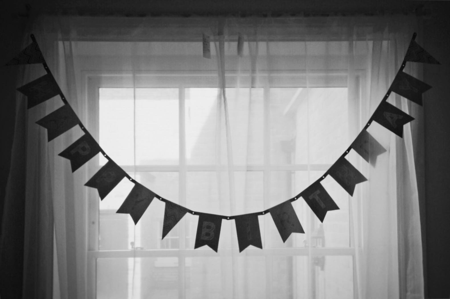 Black and white photo of 'Happy Birthday' bunting hung across a window.