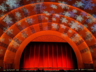 Red curtain on the main stage with giant snowflakes projected on the arches, Radio City Music Hall, New York, New York