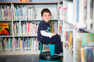 elementary age male student sitting on a stool in a library