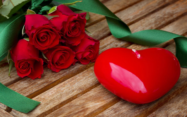 Rode kaars in de vorm van een liefdes hart en rode rozen