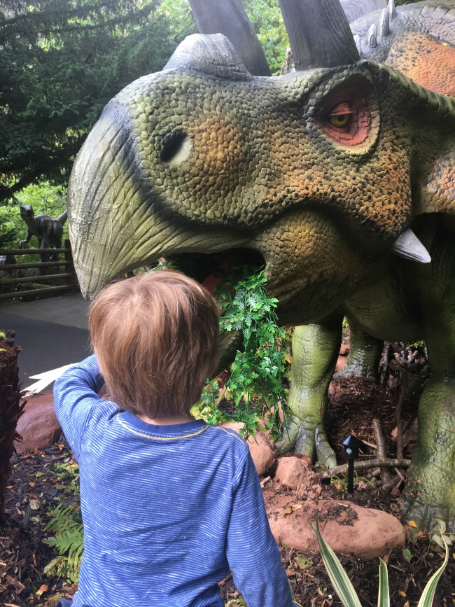a-toddler-explores-dan-yr-ogof-boy-with-hand-in-dinosaurs-mouth