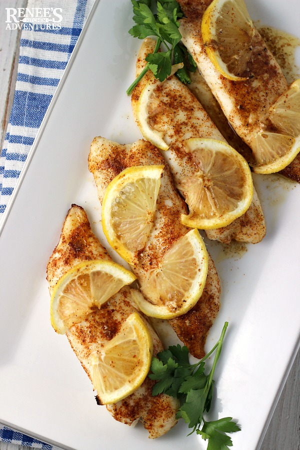 Cajun Baked Tilapia Loins by Renee's Kitchen Adventures on a white platter with lemons