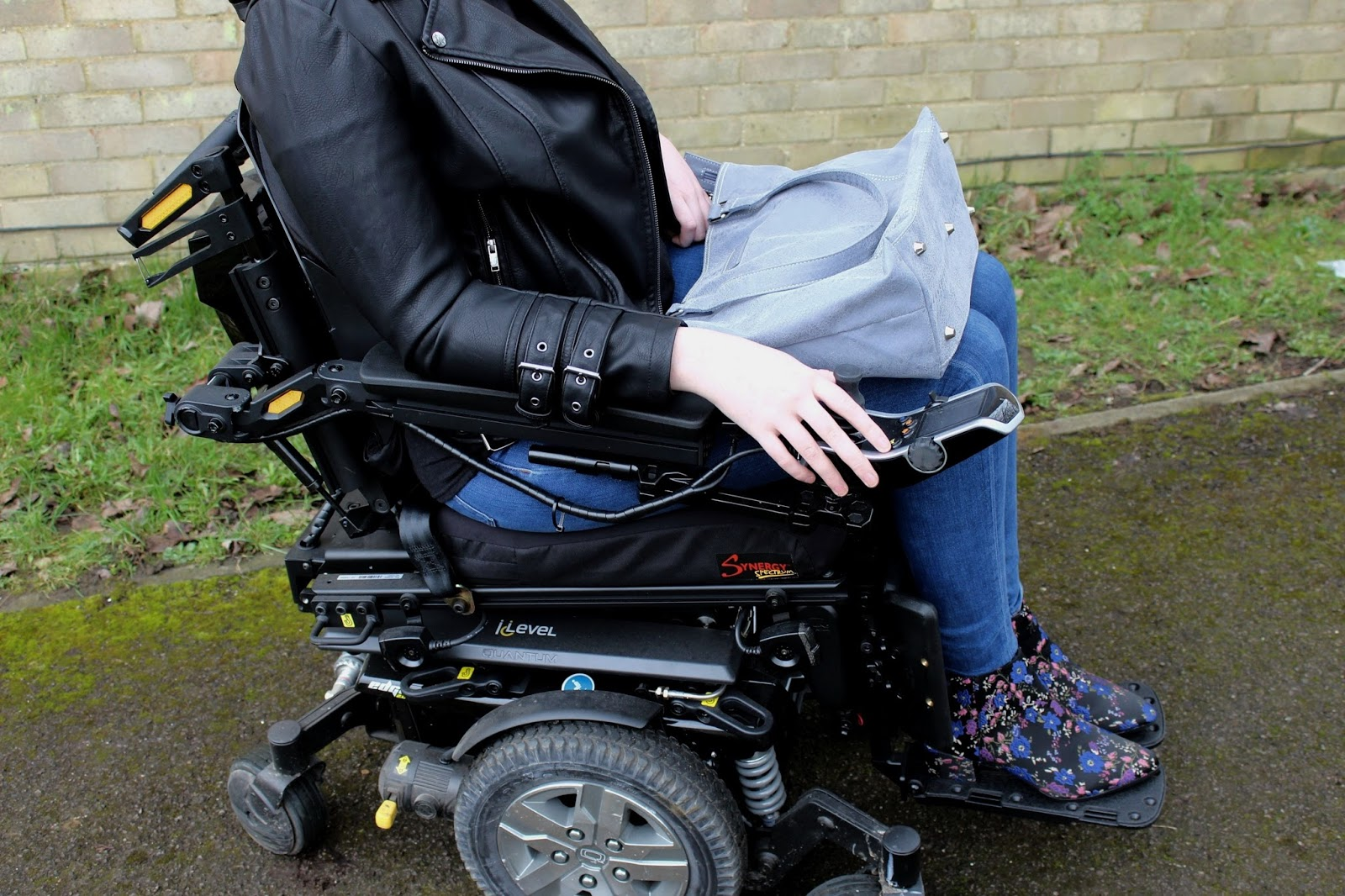 Shona is sitting in her powerchair, a large grey handbag rests on her lap.