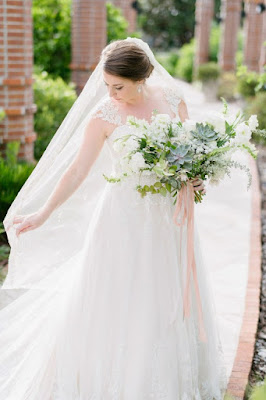 bride in wedding gown and bouquet featuring veil