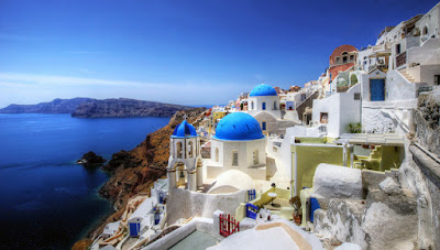greek hillside with white buildings and bright blue roofs on the coast with view of the sea