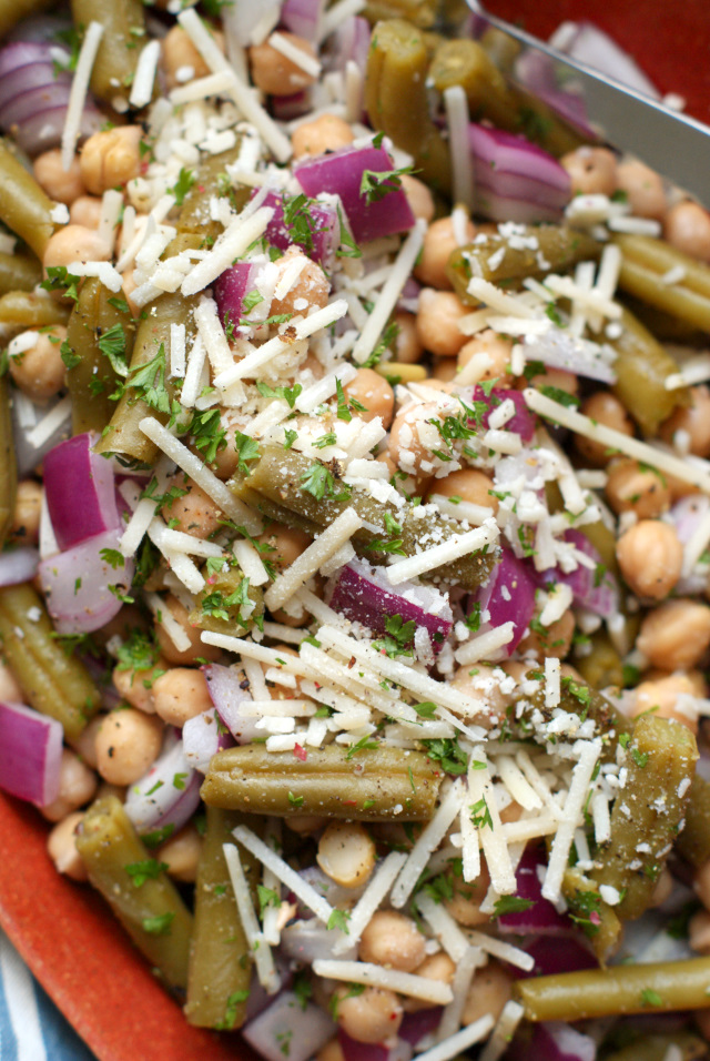 This Lean Bean Salad is the easiest to make no-cook side dish out there featuring two kinds of beans, red onions, parmigiano-reggiano cheese, and fresh herbs all tossed in a sweet and zippy dressing.