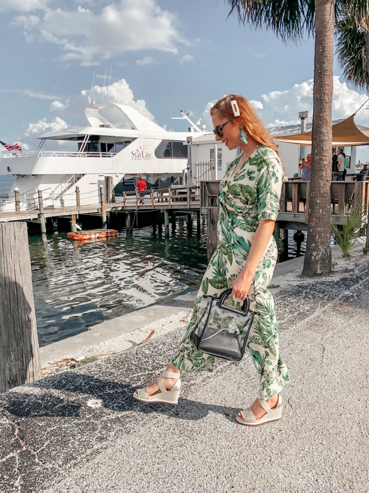 tampa blogger affordable by amanda wearing a yellow and green palm print jumpsuit from bealls outlet. she is walking in front of the starlite cruise ship. she is holding a clear bag from Target and wearing platform tommy hilfiger espadrilles from bealls outlet.