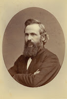 An oval portrait photograph of Charles A. Young, arms crossed, with a full beard and mustache. He looks to be in his mid-40s.