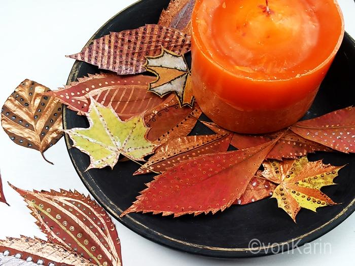 bunte herbstdeko - bemalte Baumblaetter und orange Kerze