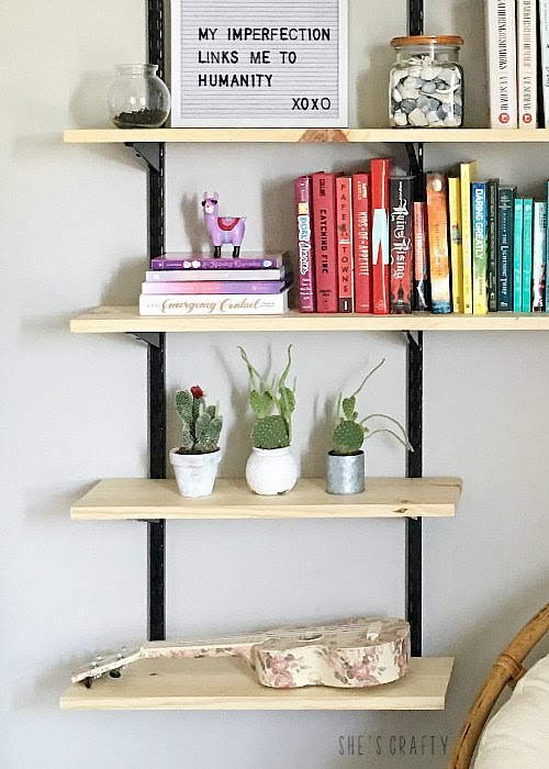 Styling open wall shelves in teen room with cactus, letterboards and books