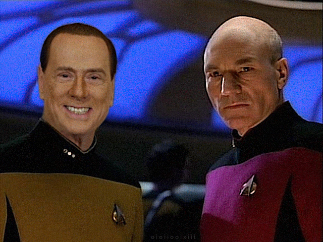 A still image from an episode of Star Trek: The Next Generation. Data and Captain Picard look at a console on the ship's bridge. Data's head has been replaced with Silvio Berlusconi's face in heavy makeup.
