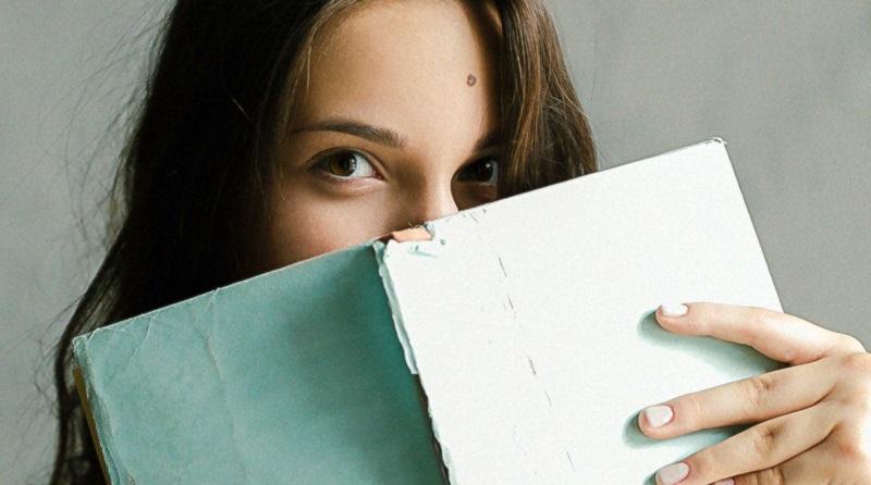 Mulher segurando um livro mostrando a capa velha e rasgada